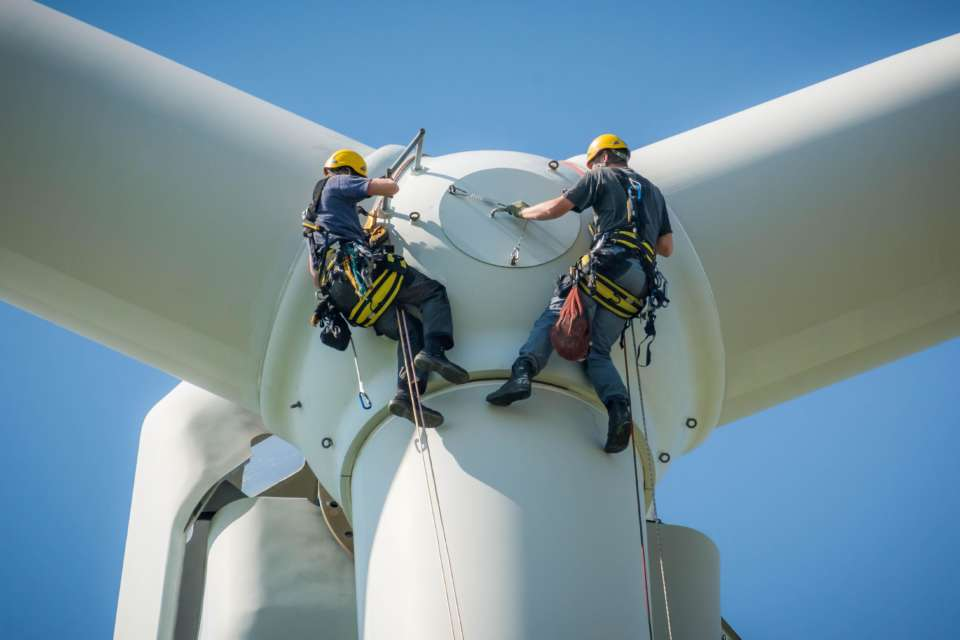 Workers suspended from a wind turbine offshore
