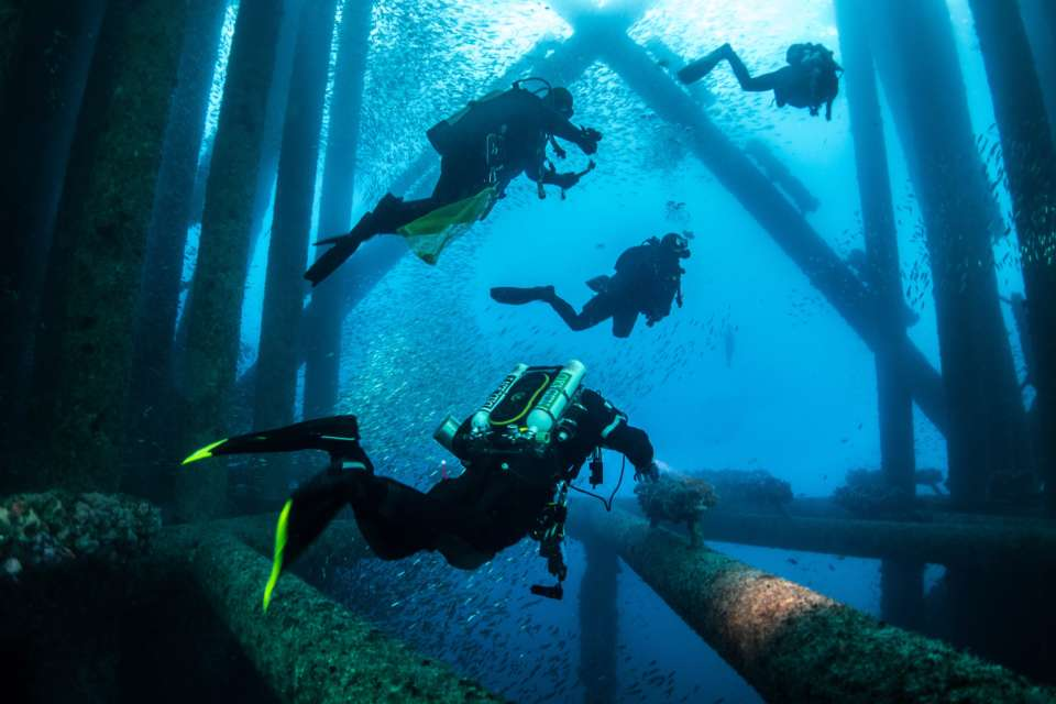 Divers under offshore oil platform